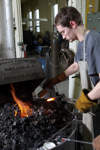 Michael Knofczynski inserts a blacksmithing tool into the hot fire.