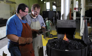 Engineering instructor Jason Prout, left, examines the blacksmithing work of Guzinski.