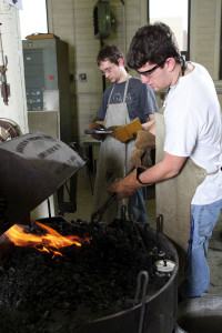 Logan Janssen, right, inserts a blacksmithing tool into the hot fire as Michael Knofczynski holds a tool for his turn at the forge.