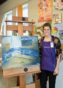 Stuart stands next to her depiction of an empty Frost Arena. A member of the women's basketball team, Stuart chose to paint Frost Arena when challenged to paint a place filled with emotion.