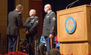 Sgt. Richard Bogue, center, shakes hands with Col. Stan Carrigan after receiving his Purple Heart Medal at the ceremony in the Performing Arts Center at South Dakota State University. Bogue, of White, is a May 2014 graduate of SDSU. At right is Staff Sgt. Walter Scott.