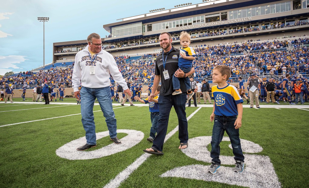 Thank you Dana: Dana J. Dykhouse, at left, is joined by his son and grandchildren before the coin toss. Dykhouse was honored at halftime for his contributions to the Dana J. Dykhouse Stadium.